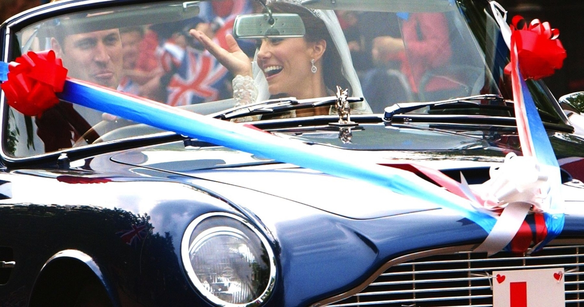 Prince William sticks his tongue out next to his wife, Kate, the Duchess of Cambridge, waving to the crowd as he drives his father, Prince Charles' Aston Martin Volante sports car.</p>