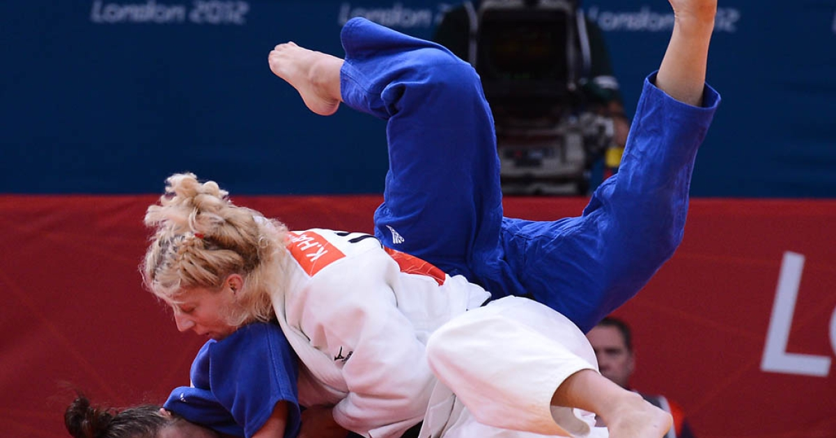 United States' Kayla Harrison (white) competes with Hungary's Abigel Joo (blue) during their women's -78kg judo contest match of the London 2012 Olympic Games on August 2, 2012 at the ExCel arena in London. Harrison won the first gold medal in judo for the US.</p>