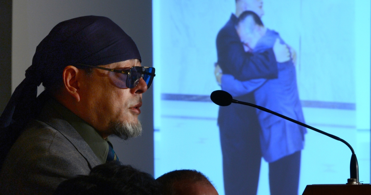 Kenji Fujimoto, former personal chef of late North Korean leader Kim Jong Il, speaks as a projector displays the cover of his book showing Fujimoto hugging North Korean leader Kim Jong Un, in Tokyo on Dec. 6, 2012.</p>