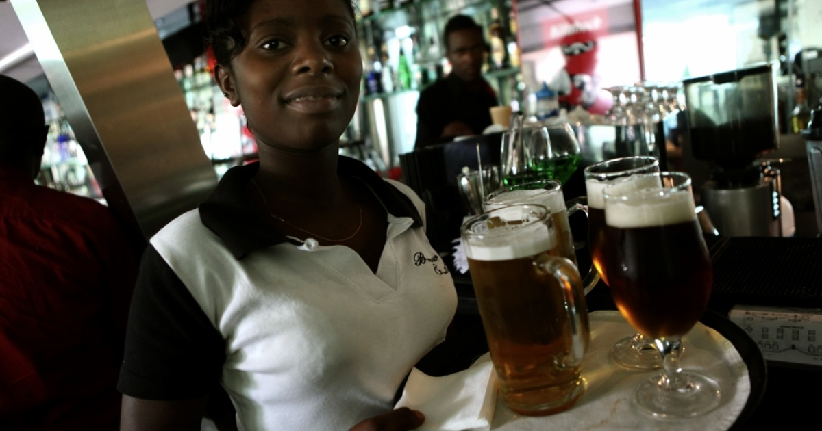 A waitress serves beer in East Africa.</p>