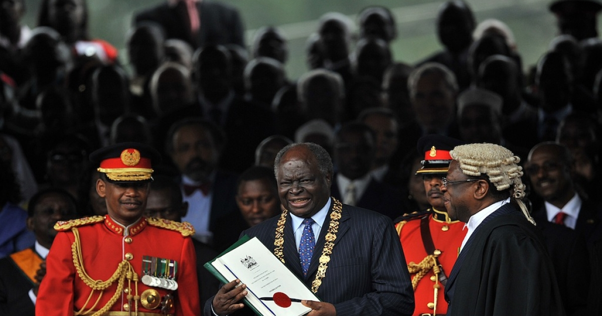 Kenya's President Mwai Kibaki (C) smiles after being handed the signed constitution document by Attorney General, Amos Wako (R) on Aug. 27, 2010 as Chief of General Staff Jeremiah Kianga (L) looks on during the promulgation ceremony for Kenya's new constitution in the capital, Nairobi.</p>