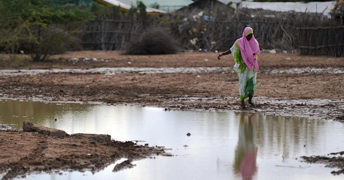 A Somali woman at Kenya's border with Somalia makes her way through a large rain puddle on October 15, 2011 following heavy rains.</p>