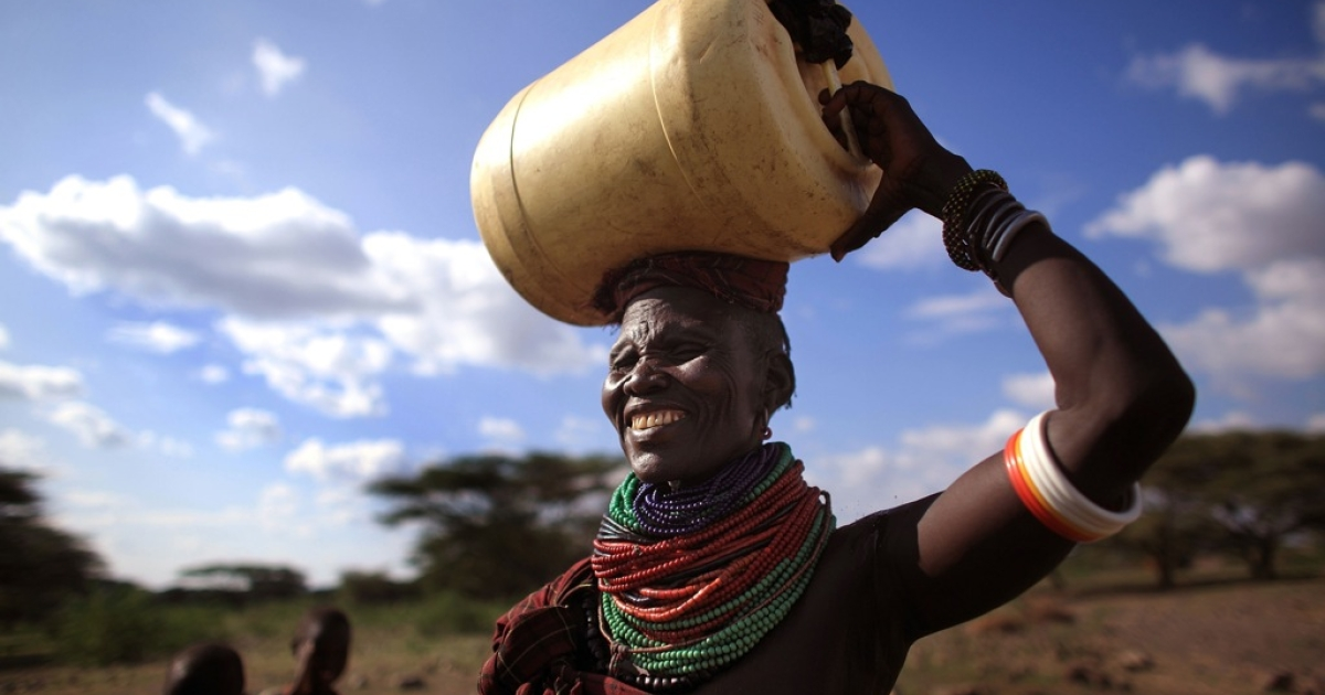 A woman from the remote Turkana tribe in Northern Kenya carries water from a well.</p>