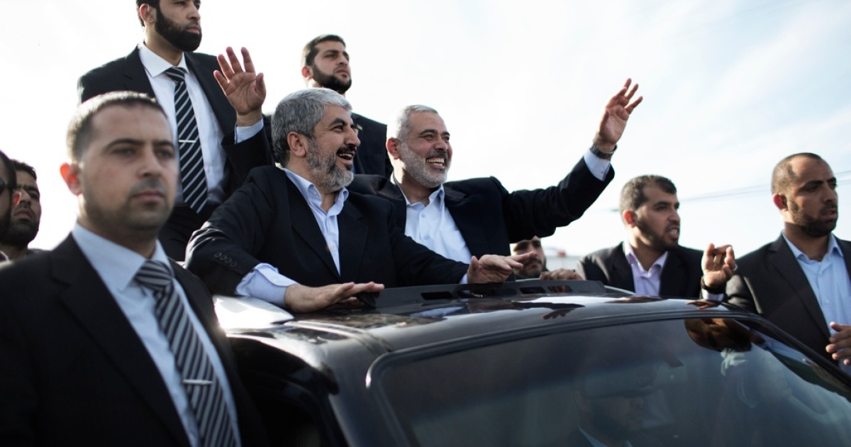 Hamas leader-in-exile Khaled Mashaal (C-L) and Hamas leader in the Gaza Strip Ismail Haniya (C-R) wave from the rooftop of a vehicle during a parade following Meshaal's arrival in Rafah, southern Gaza, on December 7, 2012. Meshaal is making his first-ever visit to the Gaza Strip amid tight security for festivities marking the ruling Islamist movement's 25th anniversary.</p>