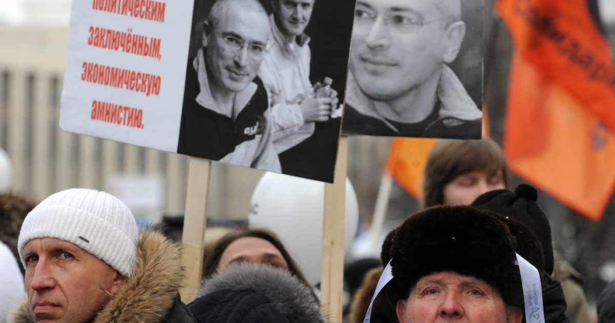 People hold portraits of jailed oil magnate Mikhail Khodorkovsky as they protest against the December 4 parliament elections in Moscow, on December 24, 2011.</p>
