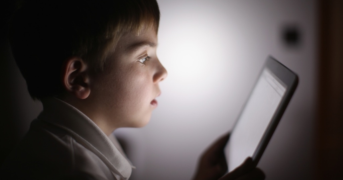 A ten-year-old boy uses an Apple iPad tablet computer on November 29, 2011 in the UK. Facebook is testing out technologies that would allow children 13 and under to use the site.</p>