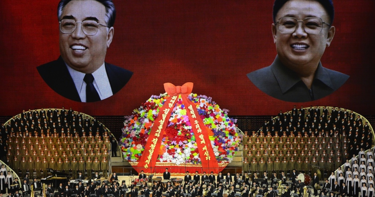 North Korean performers sing in front of portraits of founding president Kim Il-sung (L) and his son Kim Jong-il during celebrations to mark the 100th anniversary of the birth of Kim Il-sung in Pyongyang on April 16, 2012.</p>