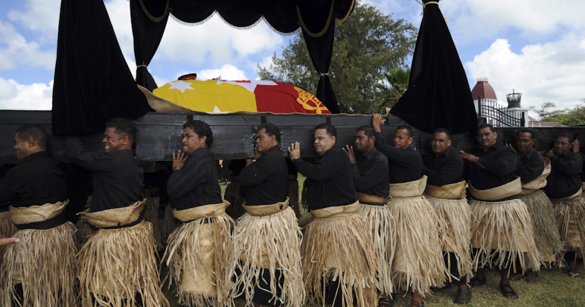 The royal standard draped casket of King George Tupou V is conveyed by the bearer party from the Royal Palace (R) on a black and gold catafalque during the king's funeral procession through the capital Nuku'alofa on March 27, 2012.</p>