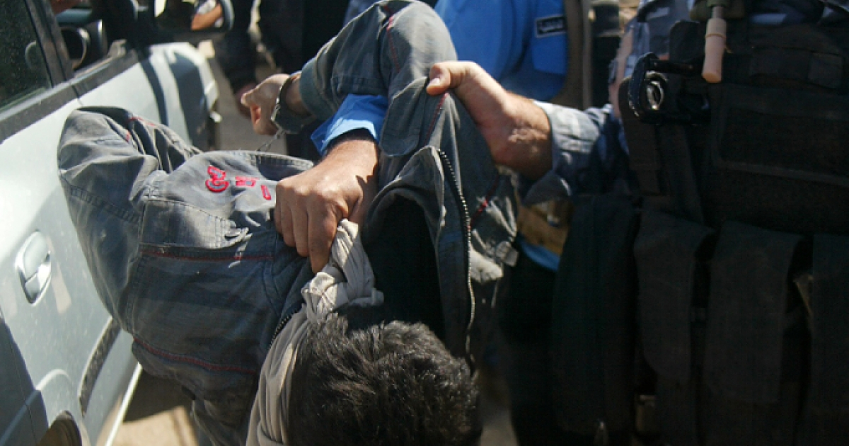 Iraqi policemen drag a man suspected of being among 19 detainees who escaped from a prison in the northern Iraqi city of Kirkuk on March 23, 2012.</p>