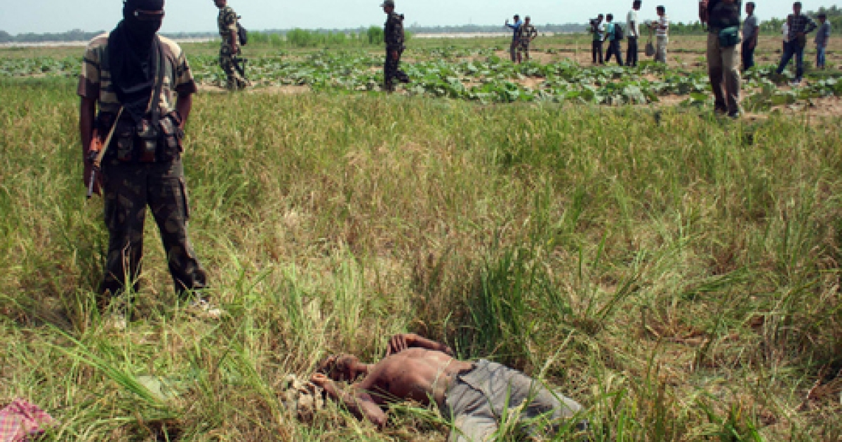 Indian paramilitary soldiers watch over the body of a suspected Maoist after an encounter at the village Bandarboni, close to Lalgarh on September 25, 2010. Indian media reported late Thursday that government forces had slain one of the Maoists' top leaders, Kishenji, in West Bengal.</p>