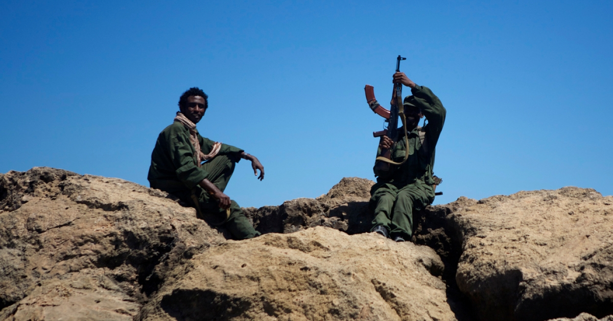 Two Ras Kamboni Brigades fighters rest on the sea wall at Kismayo port.</p>