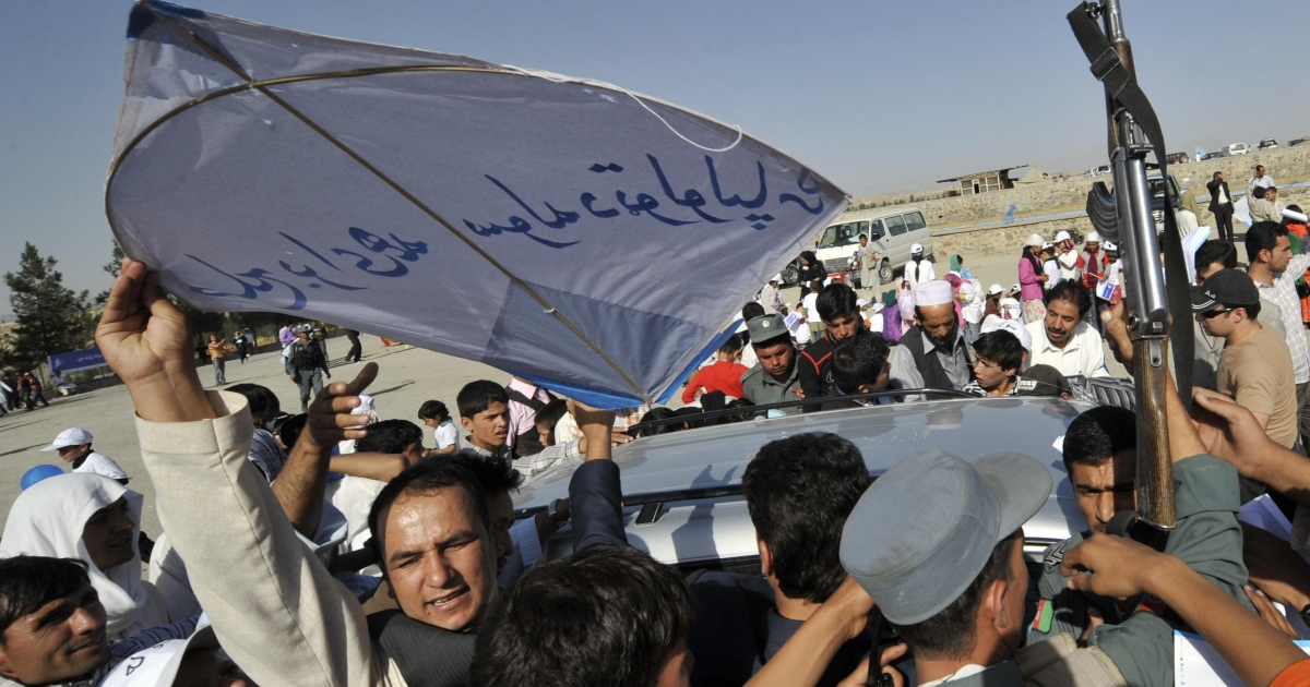 Afghan men and boys battle police for access to kites adorned with slogans promoting peace in September, 2009.</p>