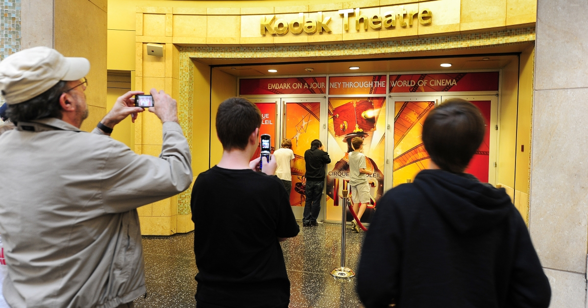 Tourists take snapshots outside the Kodak Theatre on May 1, 2012 in Hollywood, California, the venue that hosts the annual Oscars show which was renamed the Dolby Theatre on May 1, 2012, after the audio pioneer gained naming rights previously held by the bankrupt camera company Kodak.</p>