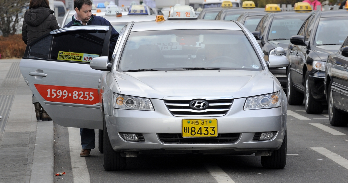 A man gets on a taxi in downtown Seoul on January 24, 2010.</p>