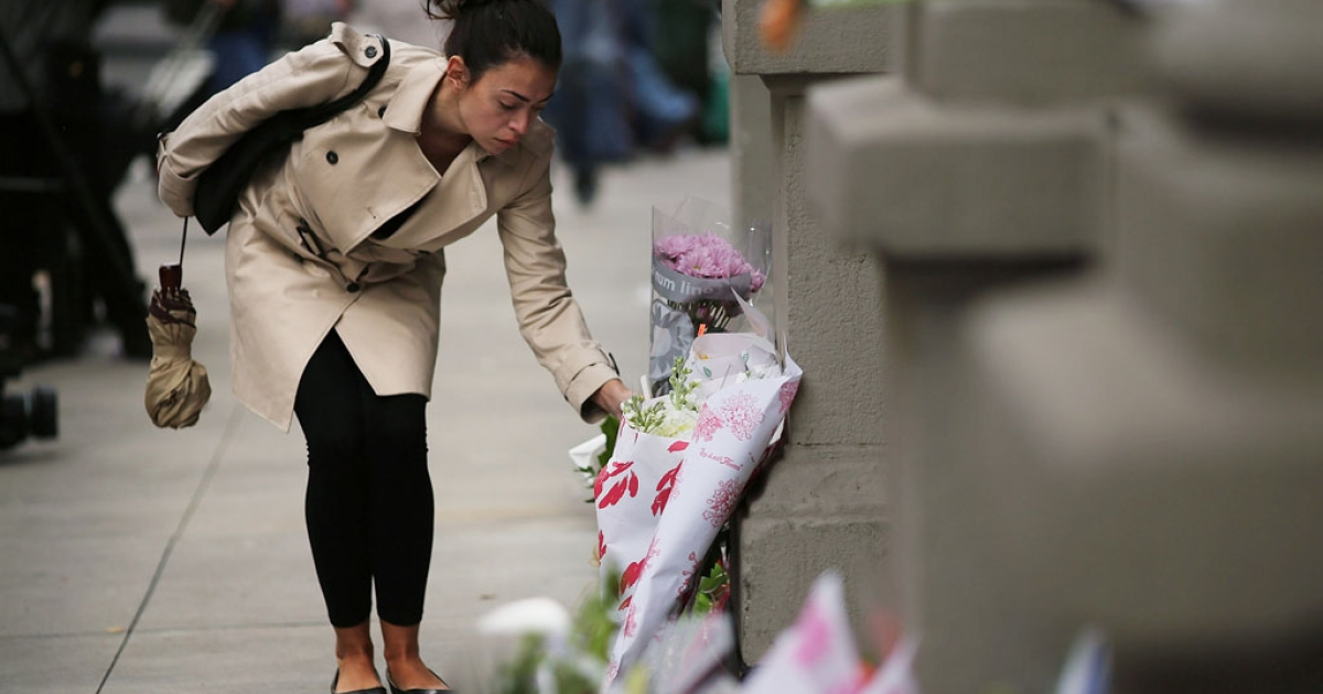 A woman leaves flowers at the building where two Krim children were stabbed to death on October 25, 2012, in New York City. Their nanny, 50-year-old Yoselyn Ortega, pleaded not guilty to murder charges on November 28, 2012.</p>