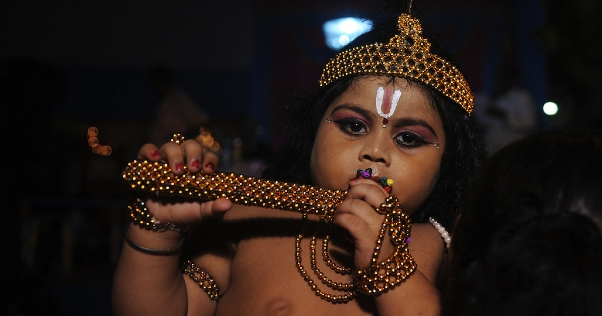 A young Indian Hindu devotee dressed as the Hindu God Lord Krishna stands amidst his family members before a fancy dress competition held at a local temple in Kolkata on August 9, 2012 on the eve of 'Krishna Janmashtami'. The Janmashtami falls on August 10 this year, marking the birth of the Hindu God Lord Krishna.</p>