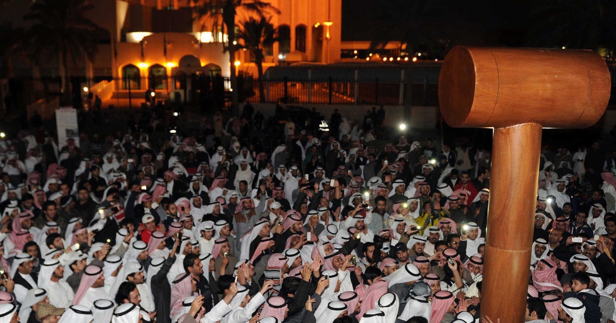 Kuwaiti opposition protesters hold a giant gavel as they demonstrate outside the Palace of Justice in Kuwait City in the early hours of November 27, 2011 against the arrest of pro-reform activists over charges of storming parliament last week. Protesters displayed a four-metre (yard) wooden gavel saying it is a replacement for the original gavel that parliament officials accused activists of stealing, which was one of the charges. AFP PHOTO/YASSER AL-ZAYYAT (Photo credit should read YASSER AL-ZAYYAT/AFP/Getty Images)</p>