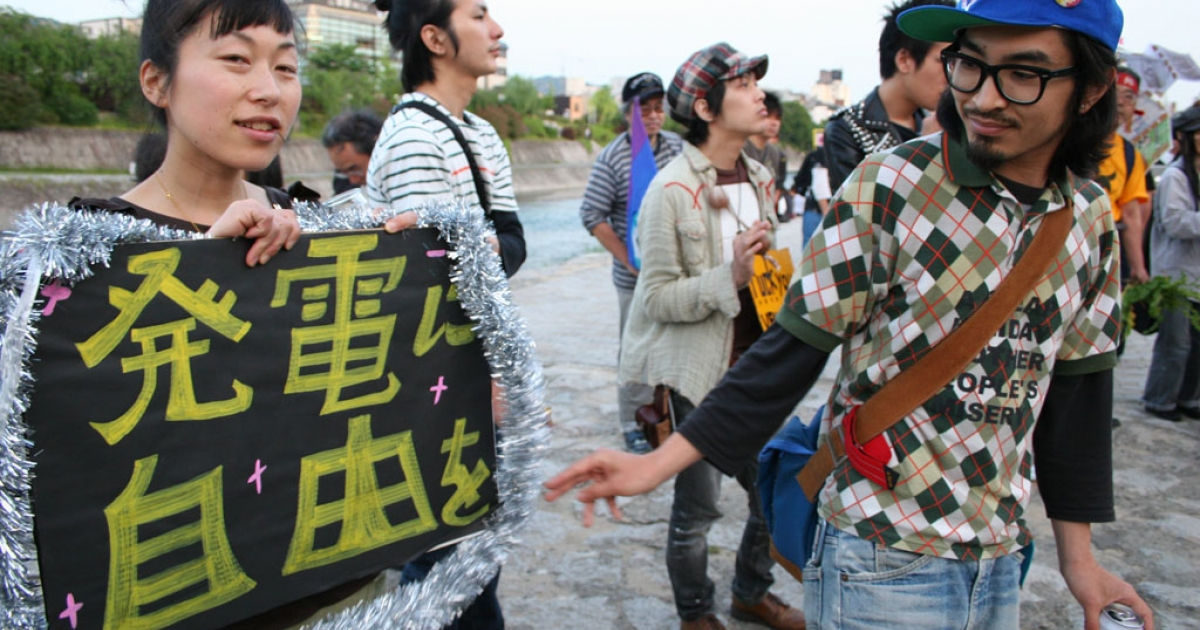 Kyoto students gather along the banks of the Kamo River to protest Japan's reliance on nuclear power. One holds a sign saying