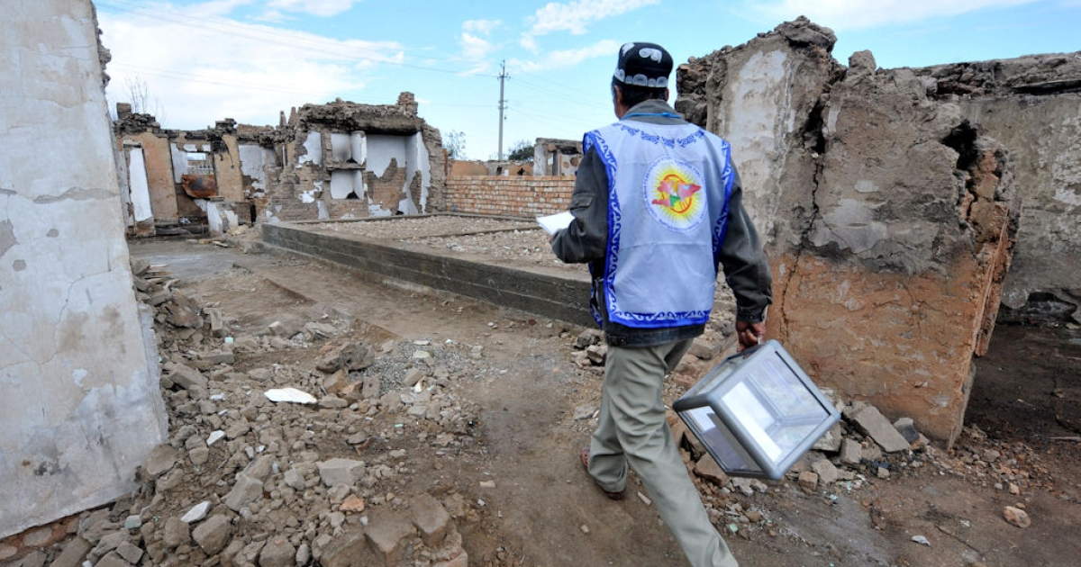 A member of the local electoral committee walks with a ballot box through the destroyed homes of ethnic Uzbeks in Osh, Kyrgyzstan on Oct. 10, 2010.</p>