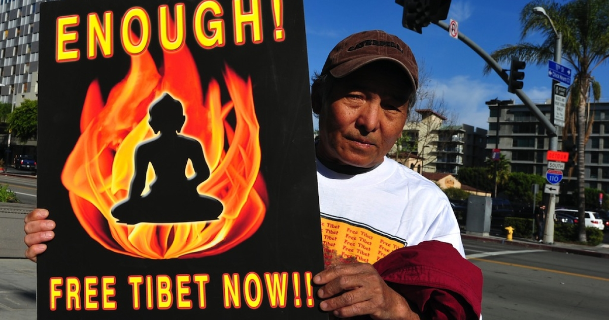 Tibetans and supporters of a 'Free Tibet' hold placards while marching on March 10, 2012 in downtown Los Angeles.</p>
