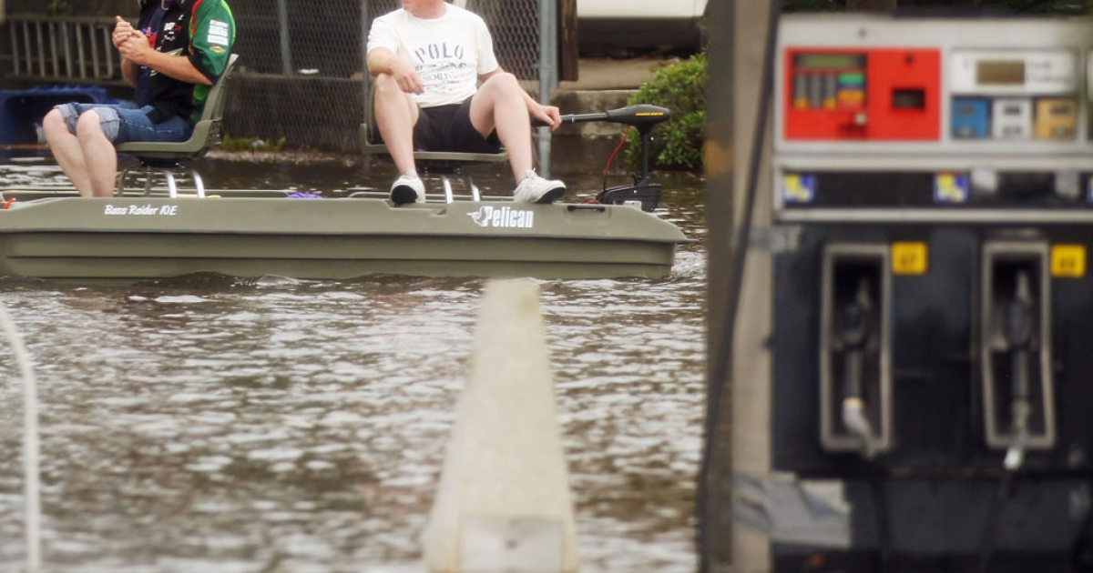 Two men in a boat pass a gas station flooded from Hurricane Isaac's storm surge on the north shore of Lake Ponchartrain on August 30, 2012 in Slidell, Louisiana.</p>