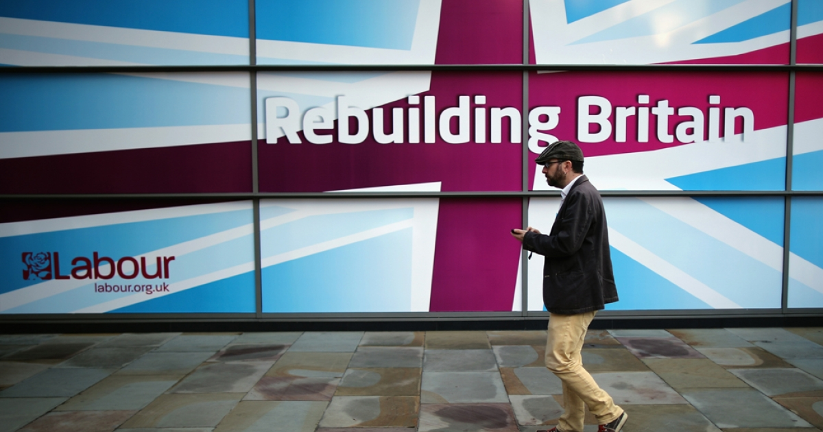 A delegate walks past a sign with the words 'Rebuilding Britain' the slogan for the 2012 annual Labour Party Conference which starts at Manchester Central on September 29, 2012 in Manchester, England.</p>