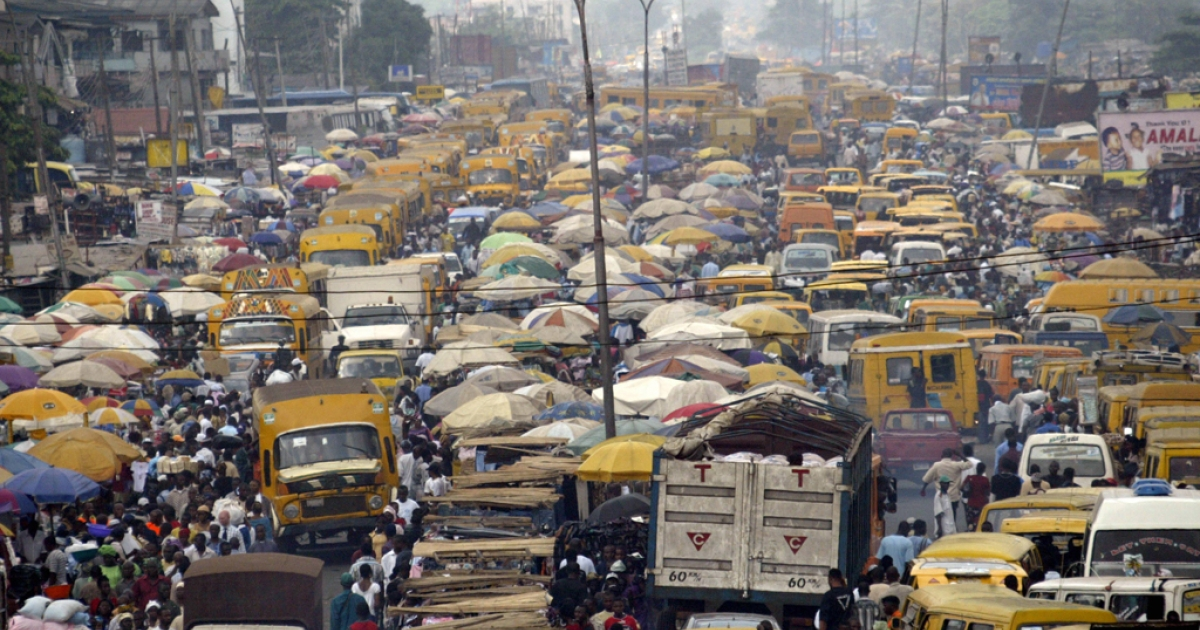 People walk struggling for space between public transport buses and trucks at the burstling Lagos bus stop.</p>