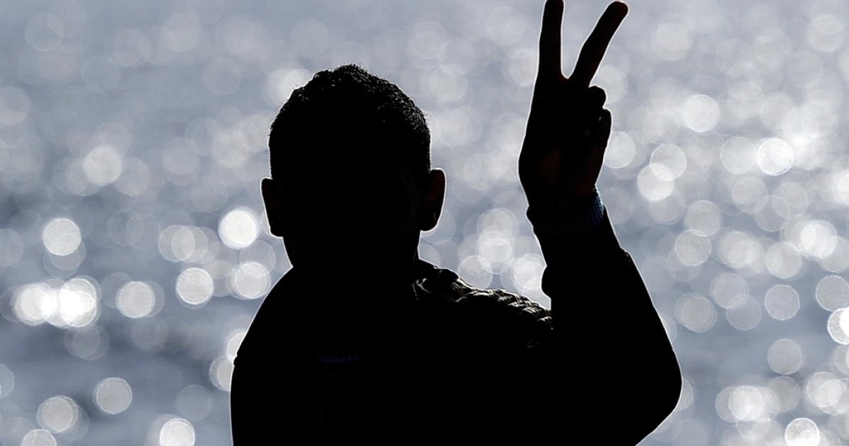 File photo of a Tunisian migrant kept in Lampedusa reception center flashing a victory sign as he waits to board on a ferry to be taken to the Sicilian city of Catania on April 12, 2011. Around 26,000 undocumented migrants have arrived in Italy so far this year, including around 21,000 who said they were from Tunisia, claiming they were fleeing a grim economic situation after the political revolution in January.</p>