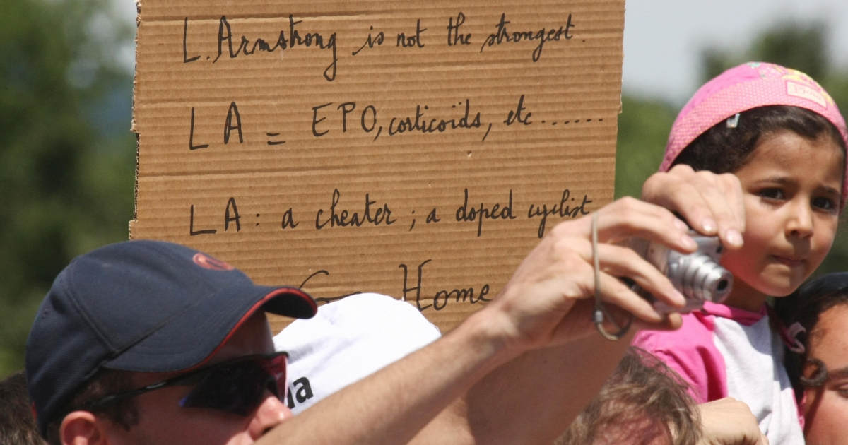 On July 24, 2009, near Bourgoin-Jallieu, France, a fan holds a sign accusing Lance Armstong, seven-time Tour de France winner, of taking performance enhancing drugs.</p>