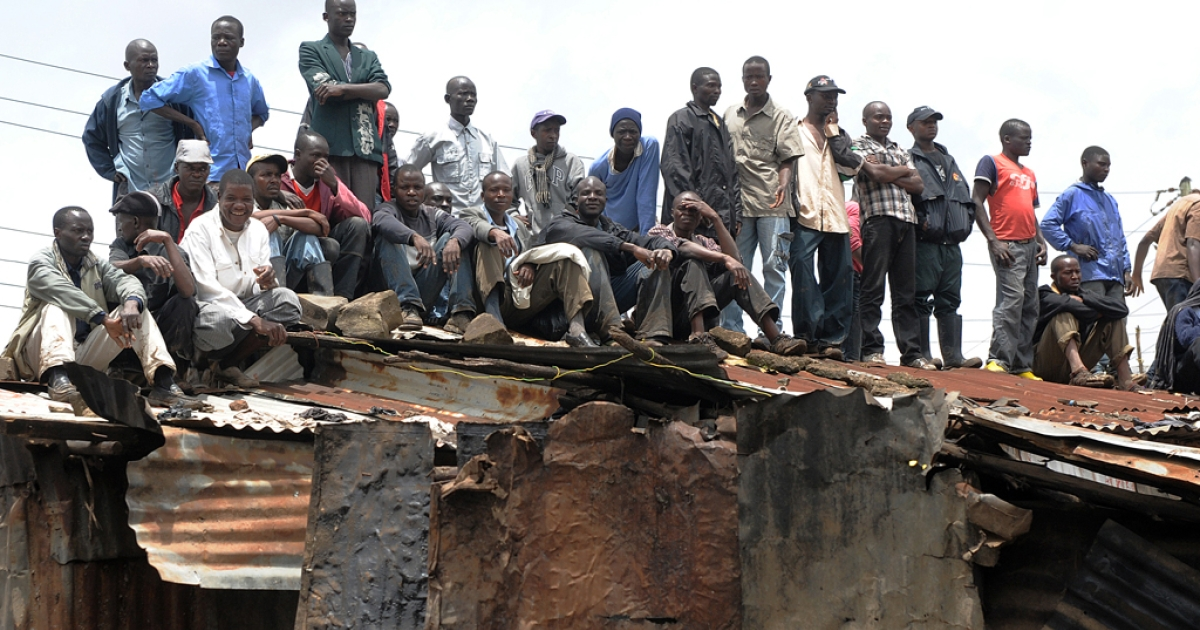 People watch from an iron sheet houses as rescuers retrieve bodies from the rubble following a massive boulder that crashed onto houses April 4, 2012  in the Mathare slum of Nairobi, killing at least six people and trapping many underground after a night of heavy rains.</p>