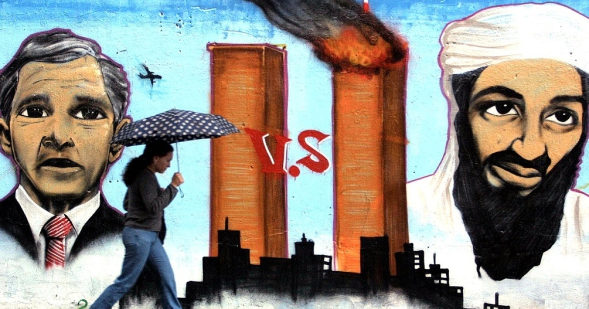 A woman walks past a wall painted with graffiti representing the Sept. 11 terrorist attacks and images of then-U.S. President George W. Bush and Osama bin Laden, on Oct. 9, 2001, in Sao Paulo.</p>