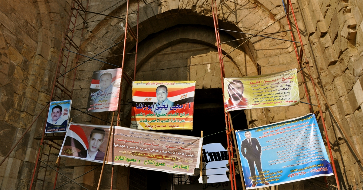 Advertisements for parliamentary candidates hang from scaffolding in Cairo in October 2011.</p>