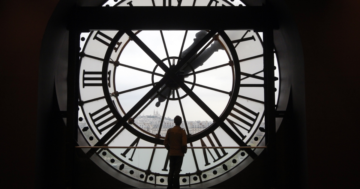 A man looks at the Seine river through the giant clock of the Orsay Museum in Paris, France, on Oct. 12, 2011.</p>