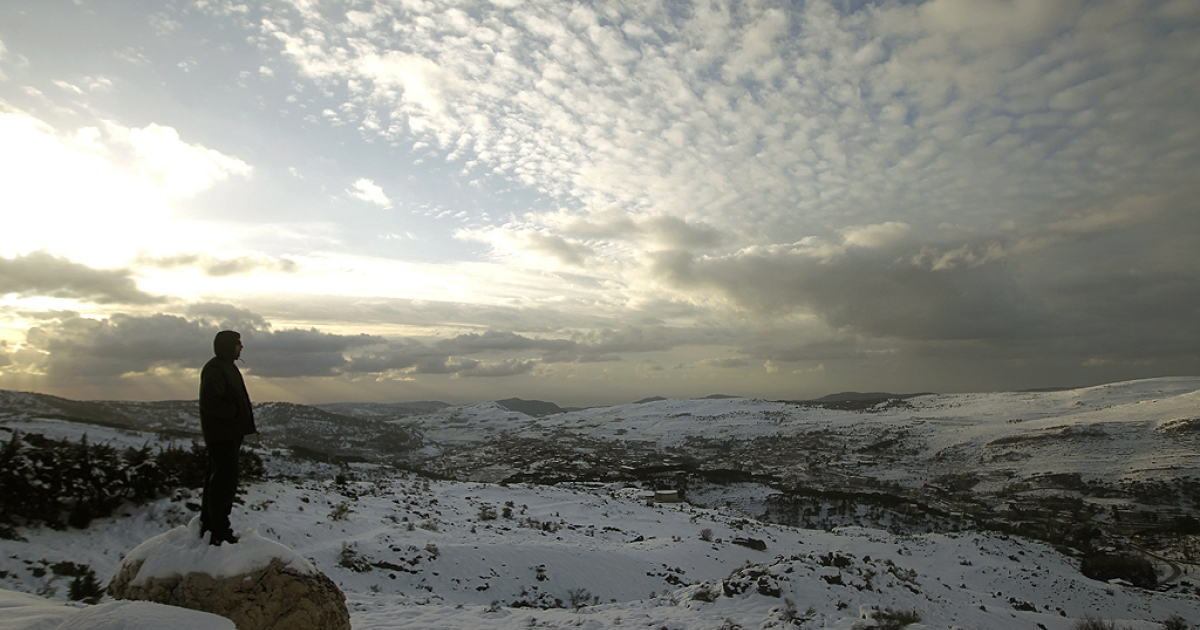 A Lebanese forest ranger observes the sunset from the cedar trees reserve of Baruk in the Shouf mountains, southeast of Beirut, following a snow storm and cold wave which hit the east Mediteranean country after several months of drought.</p>