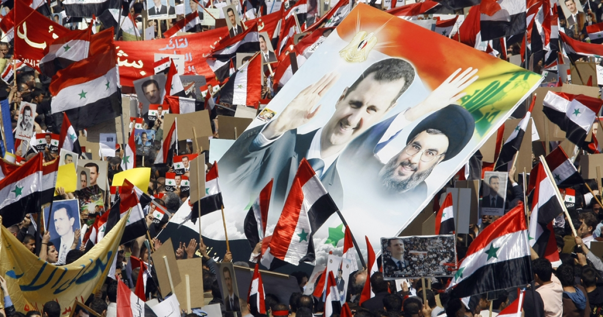 Syrians hold portraits of President Bashar al-Assad (Left) and Lebanon's Hezbollah chief Hassan Nasrallah (Right) during a rally. Hezbollah is losing support due to its unwavering support for the Syrian regime and the political fall-out of the Syrian uprising is deepening the political divides in Lebanon.</p>