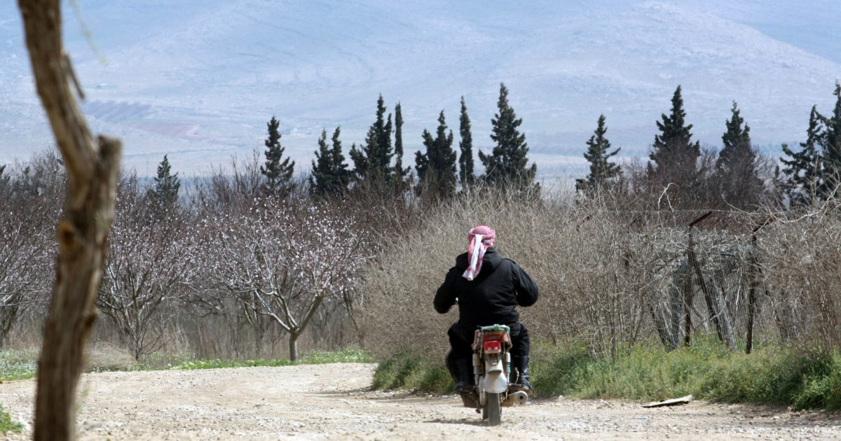 A Lebanese man rides his motorbike on March 28 in the area of Joura, only a few meters from the place where the Syrian government forces clashed with Syrian rebel troops near the al-Qaa area of the Bekaa valley on the Syrian-Lebanese border.</p>