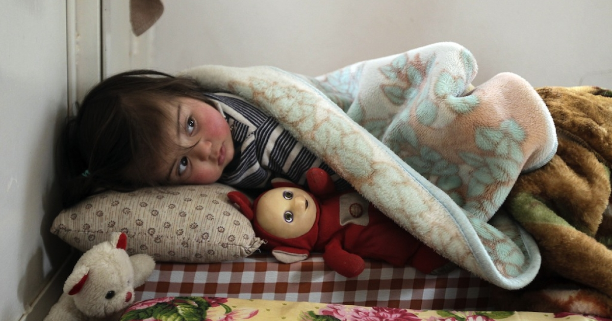 A Syrian girl who fled the violence in Syria sleeps with a doll at a shelter housing refugees in the Lebanese city of Arsal in the Bekaa Valley on March 26, 2012.</p>