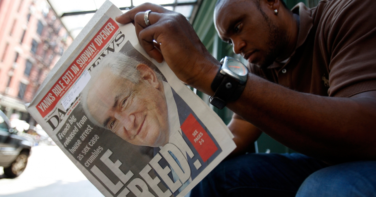 A man reads a paper with Dominique Strauss-Kahn on the front cover as media gather outside of the apartment where former IMF chief Dominique Strauss-Kahn is staying in New York.</p>