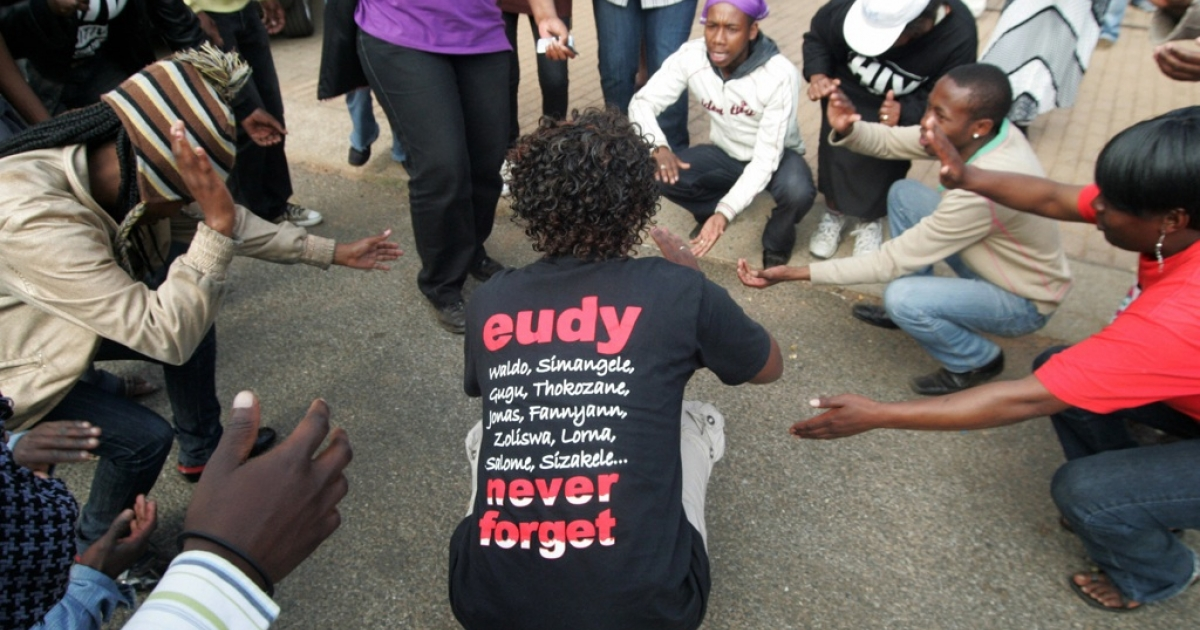 Human rights activists and supporters of the killed former South African national football team striker Eudy Simelane dance on August 27, 2009 outside the Delmas court in Mpumalanga ahead of the trial of the men accused of Simelane's gang-rape and murder.</p>