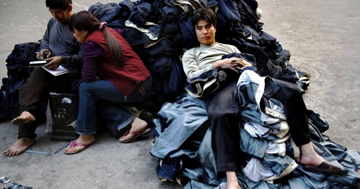 A worker sits on a pile of jeans in a garment factory in Guangzhou, China.</p>