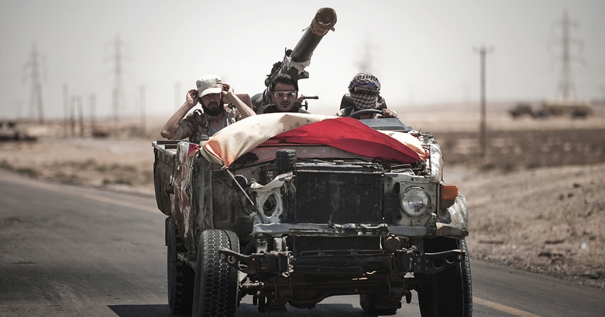 Libyan rebels drive in an armed pick-up truck towards the frontline on August 15, 2011 on the outskirt of oil port town of Brega.</p>