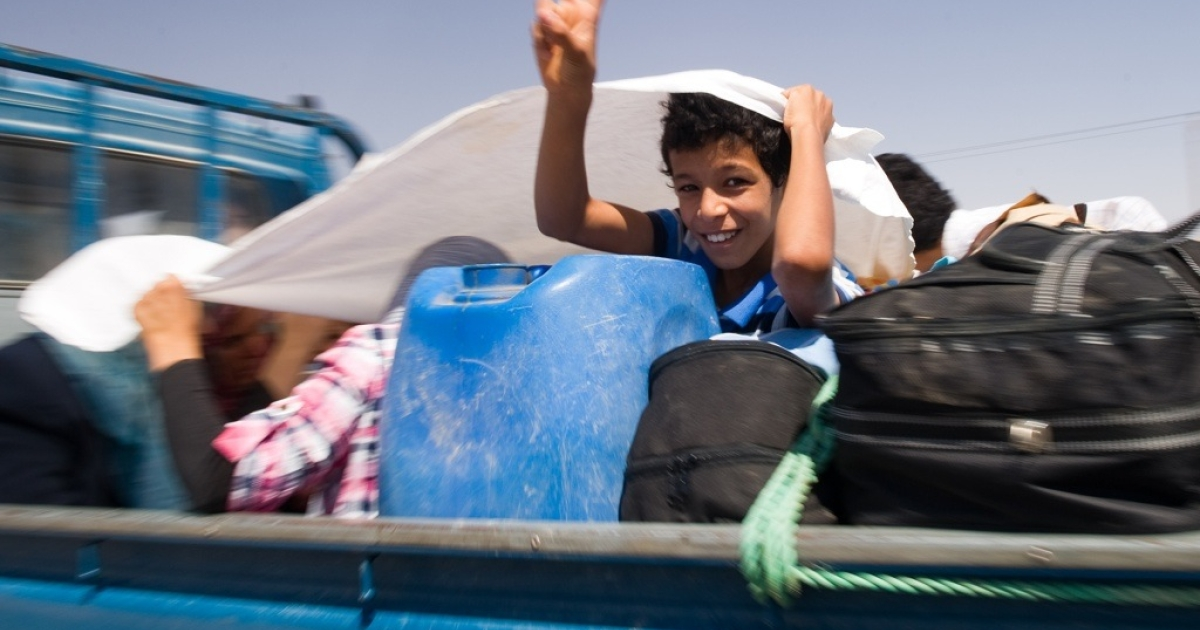A Libyan boy fleeing with his family flashes the V-sign for victory on the road out of Bani Walid on September 12, 2011. Civilians poured out of the Libyan oasis town fearful of new fighting between Muammar Gaddafi's forces and the rebel troops that have besieged the Bani Walid valley</p>
