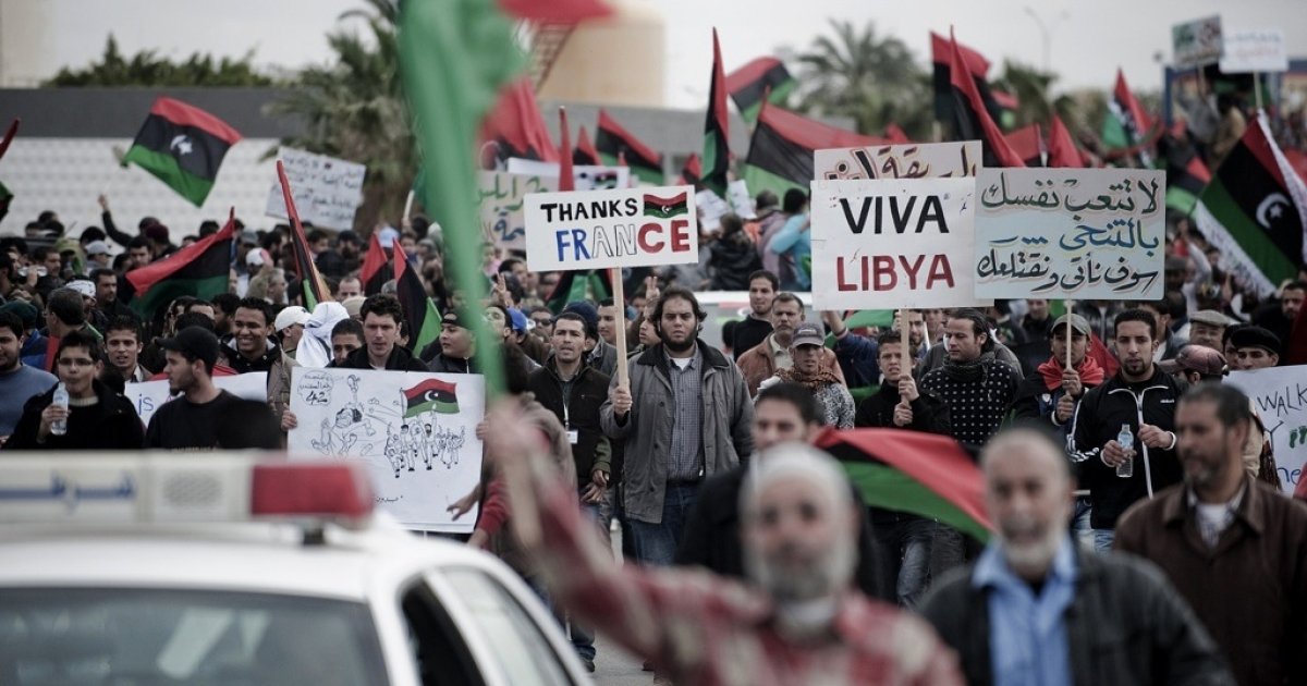 Libyan anti-government protesters hold signs and wave their country's former national flag as they march in central Benghazi on March 10, 2011.</p>