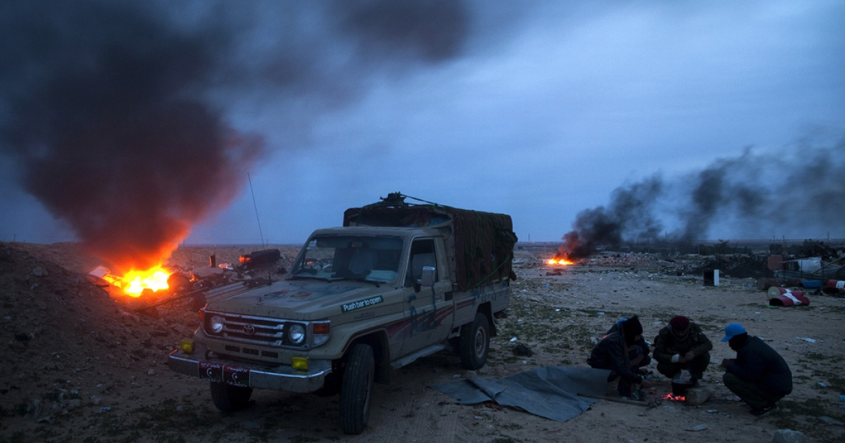 Rebel fighters make tea at the Brega checkpoint, now in government control, besides burning tires that had been lit by the fighters to provide cover from air strikes.</p>