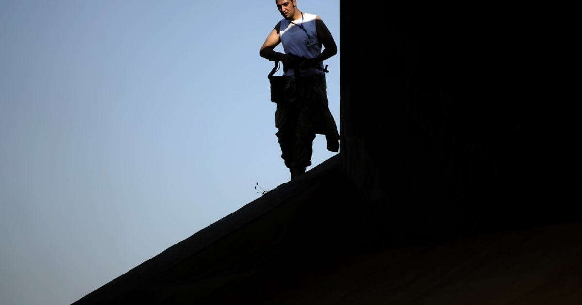 A Libyan rebel looks down from a bridge near the center of Tripoli on Aug. 21, 2011.</p>