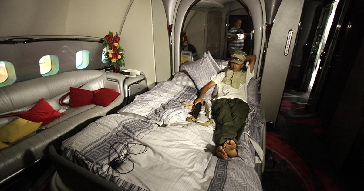 A Libyan rebel lies on the bed in Libyan leader Moamer Kadhafi's