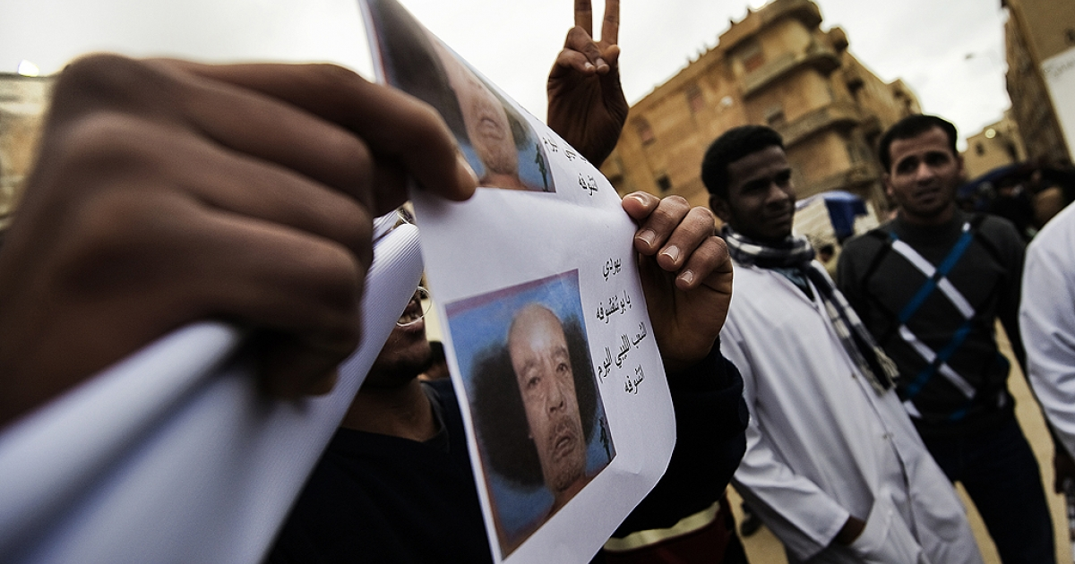 A Libyan holds pictures depicting a balding Libyan leader Moamer Kadhafi after the Muslim Friday prayers outside the courthouse in the eastern city of Benghazi on February 25, 2011.</p>
