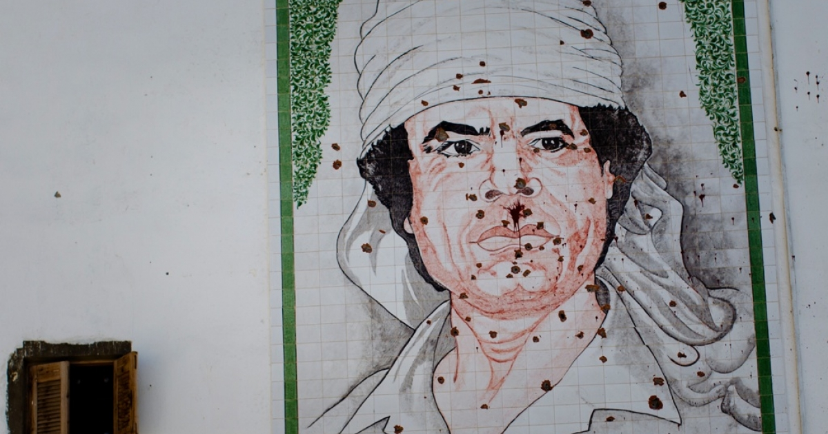 A bullet-ridden mosaic of Gaddafi is seen on the wall of a building in August 2011 in Tripoli, Libya. Gaddafi amassed billions. What will happen to them now that he's gone?</p>