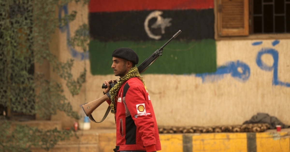 A Libyan rebel walks past a military position decorated with the rebellion flag at the southern entrance of the coastal city of Benghazi on March 15, 2011, as Libyan government forces assaulting the key city of Ajdabiya outflanked insurgents and cut off the road north to Benghazi, rebel sources said amid scenes of chaos in the town.</p>