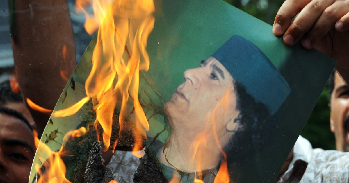 A Libyan protester burns a portrait of Libyan leader Muammar Gaddafi in front of the Libyan embassy in Kuala Lumpur on Feb. 23, 2011. Some 200 protesters gathered in front of the embassy with banners and placards to condemn the bloody crackdown on anti-government demonstrators in Libya.</p>